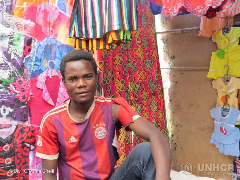 Mozambique. A refugee from the DRC sells clothes at a market stall